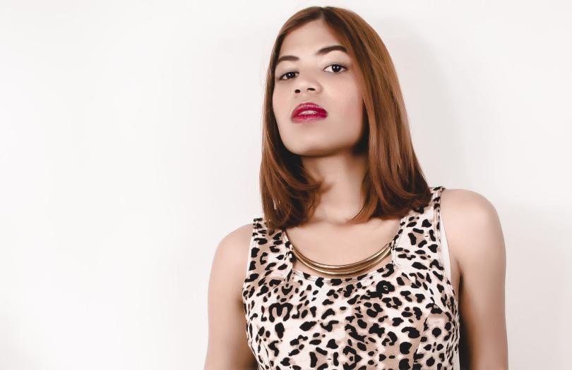 A transgender woman wearing a leopard print femme top